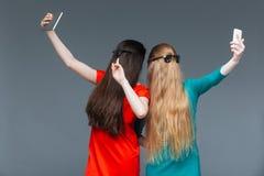 Twee omvatte vrouwen zien met lang haar en het duren onder ogen selfie stock afbeeldingen