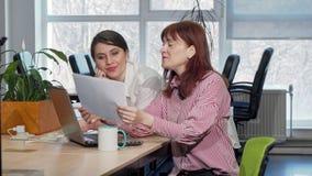Twee onderneemsters die administratie doen samen op het kantoor stock video