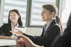 Twee onderneemsters die, en tijdens een commerciële vergadering gesturing glimlachen bespreken Royalty-vrije Stock Afbeeldingen