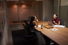 Twee onderneemsters die laat in een bureauaandeel een grap werken royalty-vrije stock foto