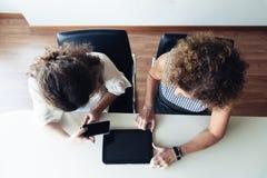 Twee onderneemsters die op kantoor samenwerken Hoogste mening royalty-vrije stock afbeelding