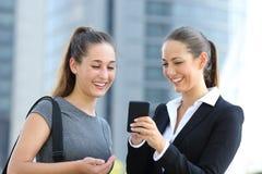 Twee onderneemsters die over slimme telefoon spreken Stock Afbeeldingen
