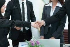 Twee onderneemsters het schudden overhandigt een bureau aangezien zij een overeenkomst sluiten royalty-vrije stock foto's