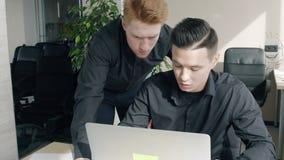 Twee ondernemers die, aan project samenwerken die bij lijst met laptop in bureau samenwerken stock videobeelden