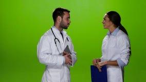 Twee ontmoetten de artsen en de bespreking over de patiënten Het groene scherm stock video