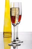Twee open vlakteglazen met gele fles Stock Foto