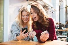 Twee opgewekte jonge meisjes die mobiele telefoons met behulp van Stock Foto