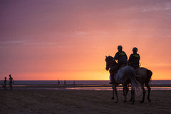 Twee opgezette Guardia Civilpolitiemannen die strand patrouilleren bij zonsondergang stock fotografie