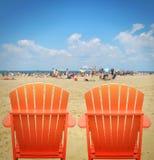 Twee Oranje Ligstoelen in Zand Stock Fotografie
