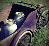Twee oude die melkblikken door een oude wagen worden vervoerd Stock Foto