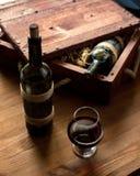 Twee oude flessen rode wijn in uitstekend krat onder het houten scheren op houten achtergrond en een kop, geselecteerde nadruk royalty-vrije stock fotografie