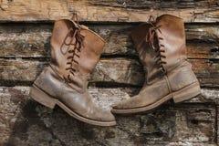 Twee oude laarzen die op een houten muur hangen Stock Foto's