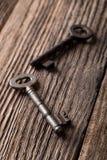 Twee oude sleutels op oude versleten houten raad Stock Afbeeldingen