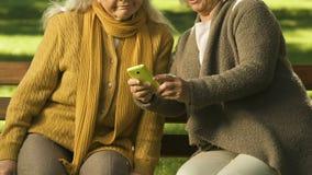 Twee oude vrouwen die die smartphone gebruiken, met moderne technologieën, het leren app wordt verbaasd stock footage