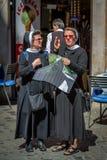Twee oudere nonnen die een stadskaart houden en aan elkaar spreken royalty-vrije stock afbeeldingen