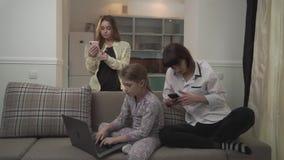 Twee oudere zusters die berichten op cel texting telefoneert het jongere meisje typen op laptop zitting op de laag in de ruimte F stock video