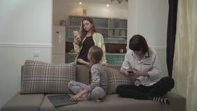 Twee oudere zusters die berichten op cel texting telefoneert het jongere meisje typen op laptop zitting op de laag in de ruimte w stock footage