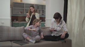 Twee oudere zusters die berichten op cel texting telefoneert het jongere meisje typen thuis op laptop zitting op de laag weinig stock video