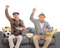 Twee oudsten die voetbalvideospelletje spelen Stock Foto