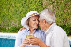 Twee oudsten met champagne bij pool Stock Afbeelding