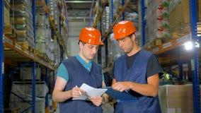 Twee pakhuisarbeiders bespreken werkplan dichtbij opslagrekken stock footage
