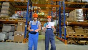 Twee pakhuissupervisors controleren de opslagcapaciteit stock videobeelden