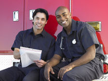 Twee paramedici die door hun ziekenwagen zitten royalty-vrije stock foto