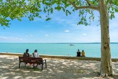 Twee Paren die in de bank zitten die aan het meer Balaton onder ogen zien royalty-vrije stock fotografie