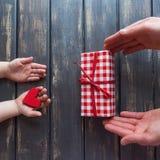 Twee paren handen, mensen en kinderen op een houten achtergrond E Royalty-vrije Stock Foto