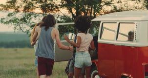 Twee paren hebben een grote tijd bij de picknick zij een retro bestelwagen naast hebben Langzame moties stock videobeelden