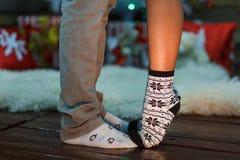 Twee paren mannelijke en vrouwelijke benen in sokken Vrouwelijke voeten tribune op de tenen op het mannelijke been Stock Afbeeldingen
