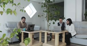 Twee paren partners die en gemeenschappelijke ruimten in een groot modern bureaugebouw werken gebruiken stock video