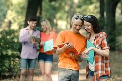 Twee paren studenten met klemborden die in het Park spreken stock foto's