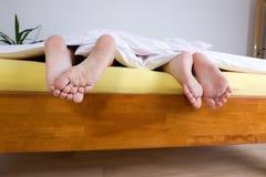 Twee paren voeten in bed Royalty-vrije Stock Foto's