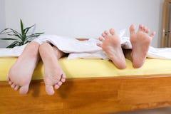 Twee paren voeten in bed Royalty-vrije Stock Afbeelding