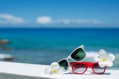 Twee paren zonnebril op achtergrond van oceaan Stock Foto's