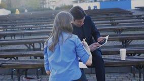 Twee partners die met notitieboekje en tablet aan de straat 4K werken stock video