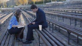 Twee partners die met notitieboekje en tablet aan de straat 4K werken stock footage