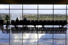 Twee passagiers die in luchthavenzitkamer wachten Royalty-vrije Stock Afbeeldingen