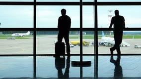 Twee passagiers die op het vliegtuigenverkeer letten door het luchthavenvenster stock videobeelden
