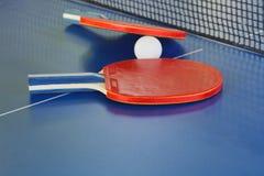 Twee peddel, tennisbal op blauwe pingponglijst Stock Afbeeldingen