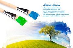 Twee penselen en landschap het schilderen stock foto