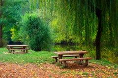Twee picknicklijsten door de rivier Stock Foto