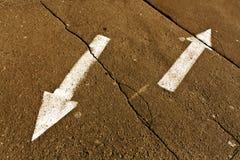 Twee pijlen op sinaasappel gebarsten asfaltoppervlakte royalty-vrije stock afbeelding