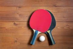 Twee pingpongrackets en een bal op een bruine houten achtergrond stock afbeelding