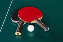 Twee pingpongrackets en een bal op een groene lijst royalty-vrije stock foto's