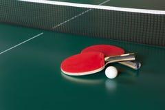 Twee pingpongrackets en een bal op een groene lijst Netto pingpong royalty-vrije stock foto's