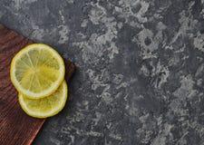 Twee plakken van citroen op een houten raad liggen op een concrete lijst Hoogste mening royalty-vrije stock foto's