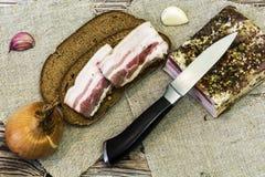 Twee plakken van gezouten bacon op een zwart brood liggen daarna op een lijst Royalty-vrije Stock Afbeeldingen
