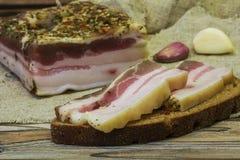 Twee plakken van gezouten bacon op zwart brood liggen op de lijst Stock Foto's
